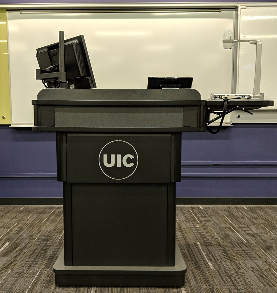 Front view of a U I C branded lectern in a classroom with multiple devices with monitors and a document camera.